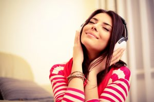 Woman happily listening to music with headphones